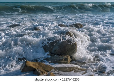 Sea waves crashing with stones on the rocks with the horizon and sky.
