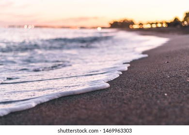 Sea waves foam in the beach at sunset