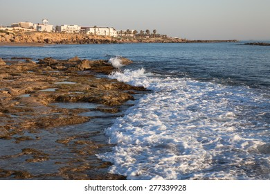 Sea waves with foam on the stony shore. Mediterranean town in the background.