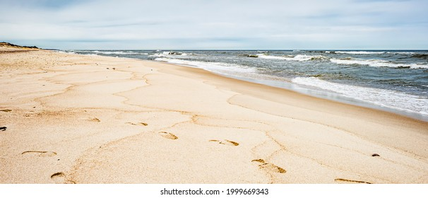 Sea waves and footprints on the sand on the beach and overcast sky - Shutterstock ID 1999669343