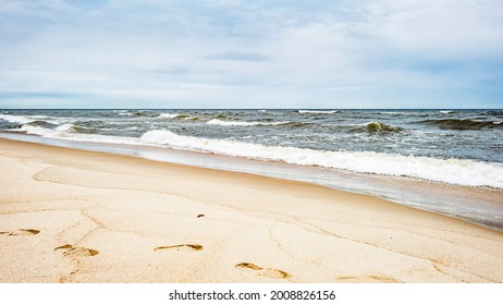 Sea waves and footprints on the sand on the beach and overcast sky - Shutterstock ID 2008826156
