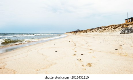 Sea waves and footprints on the sand on the beach and overcast sky - Shutterstock ID 2013431210
