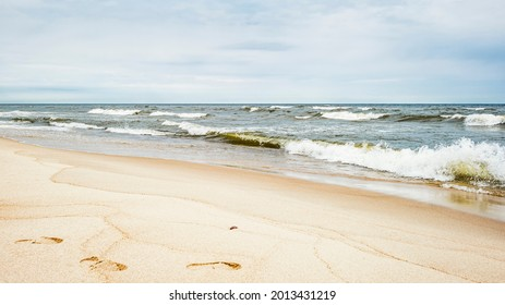 Sea waves and footprints on the sand on the beach and overcast sky - Shutterstock ID 2013431219