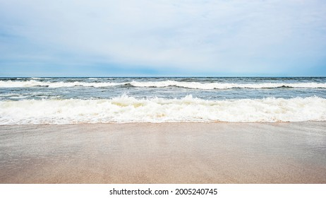 Sea waves on the beach and overcast sky - Shutterstock ID 2005240745