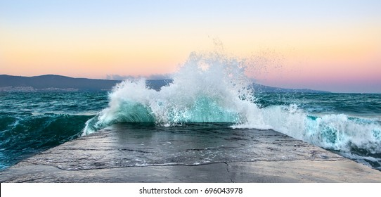 Sea waves in sunset with rocks and stones. Nature landscape.