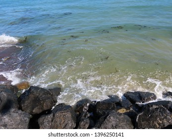 Sea waves washing against black rocks on the shore of Arromanches, D-day beach, in France, on a sunny summer day. Water is clean and transparent