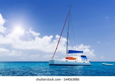 Sea yacht in azure water. Blue sky and green tropic island. Seychelles.