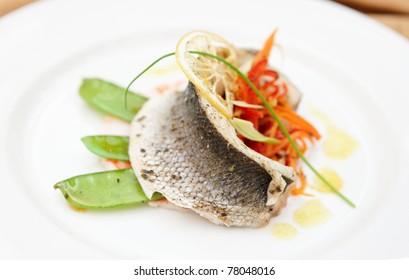Seabass haute cuisine dish with various vegetables
