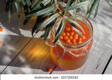 Seabuckthorn oil bottle with berries branches of sea-buckthorn