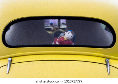 Seaburn, Sunderland / Great Britain - August 31, 2015: Vintage Noddy doll in the back of a classic yellow car looking out through the rear windscreen and smiling to the camera.
