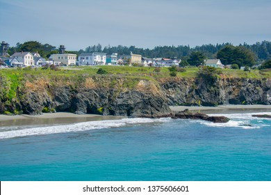 The seacoast village of Mendocino, California lines an ocean headland at low tide on a sunny spring afternoon.