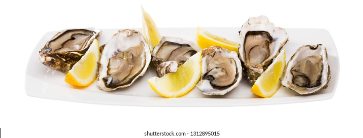 Seafood appetizer fresh oysters with lemon on white plate. Isolated over white background