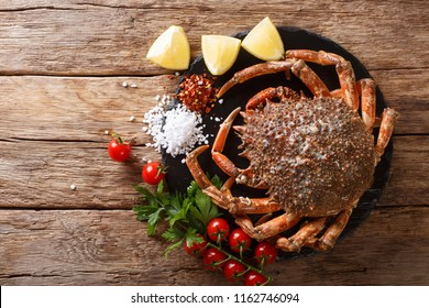 Seafood background: raw edible spider crab with ingredients close-up on a stone board on a wooden table. horizontal top view from above