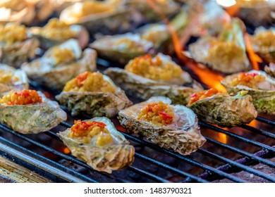Seafood barbecue placed on a ladle charcoal grilled oysters