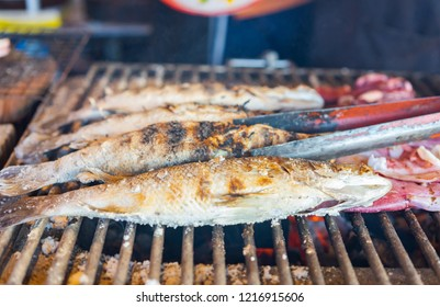 Seafood being cooked on a grill.