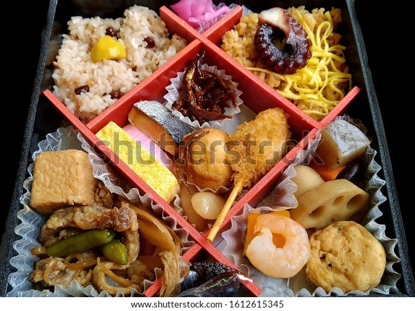 Seafood bento box with diagonal compartments from train in Japan, includes tofu and noodles and rice.