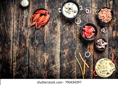 Seafood in bowls. On a wooden background.
