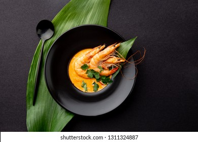 Seafood cream soup with shrimps decorated with tropical leaves. In black plate, on black background. Top view, copy space.