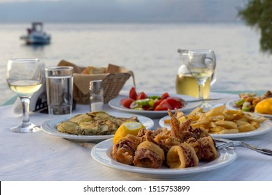 Seafood. Delicious fried calamari, french fries, cucumber, fried zucchini and tomato salad and glasses of wine in a traditional Greek tavern near the sea close-up