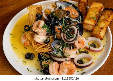 Seafood dish with shrimp, squid, octopus in garlic sauce and condiments.