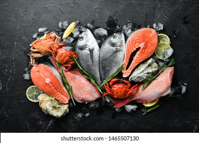 Seafood: Dorado, salmon, crab, grouper, oysters. On a black stone background. Top view. Free space for your text.