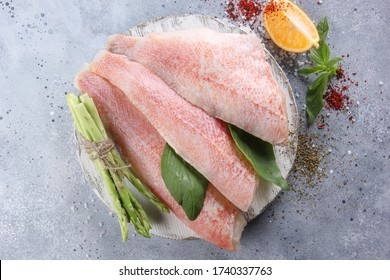 Seafood. Fish. Raw red bass perch fillet with asparagus, herbs, spices and lemon on a white wooden board on a light grey background. Flatlay, top view. Background image, copy space