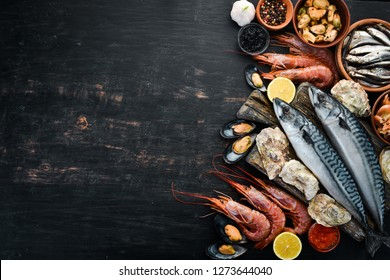 Seafood. Fresh fish, shrimp, oysters and caviar on a black wooden background. Top view. Free copy space.