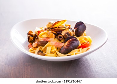 Seafood fresh homemade pasta. Italian pasta with oyster and guanciale. Mussels and prawns tagliatelle pasta. Tagliatelle spaghetti with oysters and seafood sauce. Mediterranean fres sea food dish