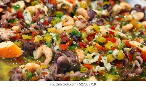 Seafood and fresh vegetables salad with octopus, shrimps, calamari squid, pepper and green herbs in brine dressing close up, high angle view