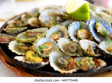 Seafood - grilled limpets served with lemon.Lapas grelhadas.Madeira's traditional dish and a typical snack of the Canary Islands.Selective focus.
