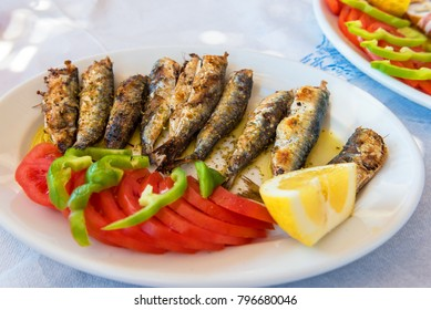 Seafood, grilled sardines served with vegetables in traditional Greek tavern. Naxos island. Greece.