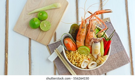 Seafood Instant noodles in the bowl, decorated with lemons and lemongrass on the wooden background. Cooking at Home. Prepare Food concept.