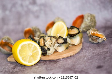 Seafood julienne served in a rapan shell with lemon on a stone sheet of slate, close-up