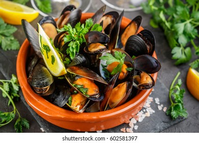 Seafood. Mussels in wine with parsley and lemon.  Clams in the shells. Delicious snack for gourmands. Selective focus