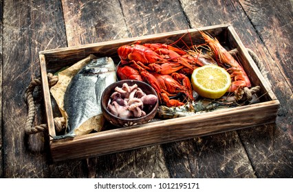 Seafood in an old tray. On a wooden background.