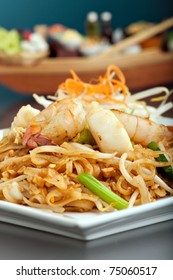 Seafood pad Thai dish of fried rice noodles on a square white plate with chopsticks and grated carrot garnish. Shallow depth of field.