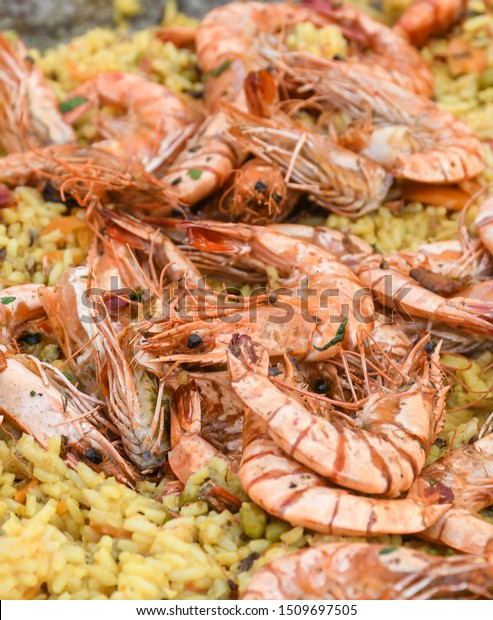 Seafood paella cooked in a large pan wok, street food festival. Mexican fiesta national day dish specialty. Live cooking station. Fresh Food Buffet Brunch Catering Dining Eating Party Sharing Concept
