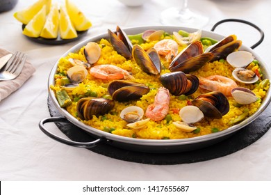 Seafood Paella, famous Spanish  rice dish in traditional frying pan. Paella valenciana with pink prawns, clams and mussels on saffron rice with vegetables.