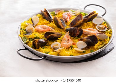 Seafood Paella with  prawns, clams and mussels on saffron rice with vegetables served in  traditional frying pan. Paella de marisco   Spanish cuisine background.