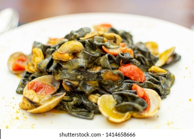 Seafood pasta dish, Italian black fettuccini with vongole clams and mussels close up
