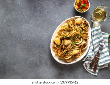 Seafood Pasta. ITALIAN SPAGHETTI ALLE VONGOLE. Clams spaghetti on white plate with white wine, gray background. Top view