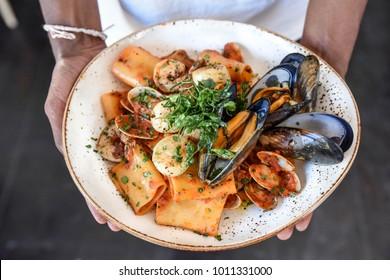 Seafood pasta served on stoneware at Italian restaurant