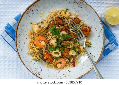 Seafood pilaf or risotto on a plate - top view