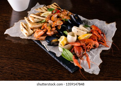 Seafood platter. Mediterranean cuisine restaurant food, fried calamari rings, king prawns, mussels, oysters, shellfish delicacy, top view on wood table background. Catering, banquet table