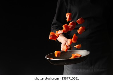 Seafood, Professional cook prepares pieces of red fish, salmon, trout. Frost in the air, Cooking seafood, healthy vegetarian food and food on a dark background. Horizontal view. Banner