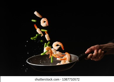 Seafood, Professional cook prepares shrimps with sprigg beans. Frost in the air, Cooking seafood, healthy vegetarian food