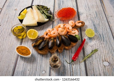 Seafood from raw shrimp mussels and pieces of cod with spices, olive oil on wooden boards.