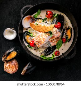 Seafood and rice noodles in cream sauce. Healthy meal made of sea bass fish, mussels, crab meat and other seafood with tomato and rice noodles. Top view.
