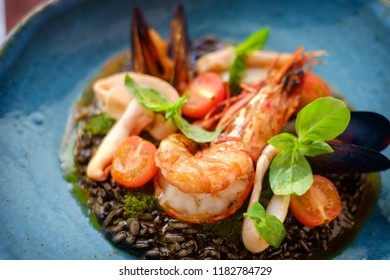 seafood risotto black on plate on a wooden background, macro