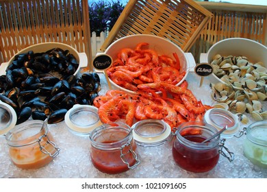 Seafood section of a buffet, with mussels, prawns and clamps, and codiments on ice